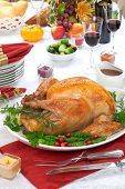 foto of horn plenty  - Garnished roasted turkey on fall festival decorated table with horn of plenty and red wine - JPG