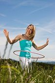 image of hulahoop  - Blond woman standing on a lawn and trained with hula hoops - JPG