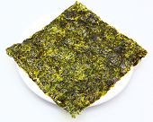 Large thin sheet of pressed seaweed pan fried in olive oil in a white plate.