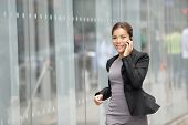 Businesswoman on cellphone running while talking on smart phone. Happy smiling mixed race Asian / Ca