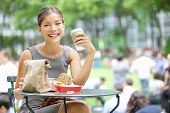 Young business woman on lunch break in City Park drinking coffee and eating sandwich. Happy smiling