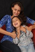 stock photo of tickling  - Sisters with Alaska Native heritage laugh with the older sister tickling the younger - JPG