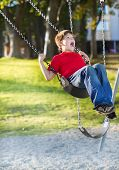 Happy Young Boy Playing On Swing