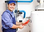 Smiling technician repairing an hot-water heater
