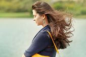 Portrait of a beautiful young brunette woman with cute tangled hair thinking