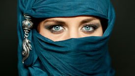 stock photo of burka  - Portrait of an arabic young woman with her beautiful blue eyes in traditional islamic cloth niqab - JPG
