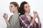 picture of peer-pressure  - Girl lighting a cigarette as another snaps one in half - JPG