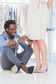Attraktive Mode-Designer sitzen und verlegen von Nadeln auf Kleid