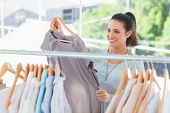 Fashion woman choosing dress in a studio