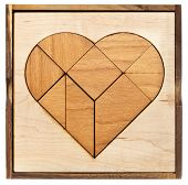 heart version of tangram, a traditional Chinese Puzzle Game made of different wood parts to build abstract figures from them, isolated on white