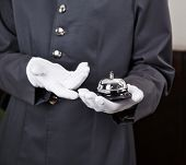 Bellboy holding bell in hotel on his hand