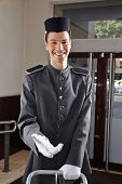 Happy concierge in uniform standing in a hotel lobby