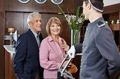 Senior couple at check-in at hotel looking at concierge