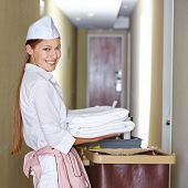 Smiling hotel maid with fresh towels doing housekeeping