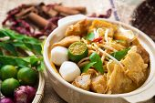 Hot and spicy Malaysia Curry Noodle or laksa  mee with hot steam in clay pot, decoration setup, serv