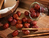 Dried red date or Chinese jujube. Traditional herbal medicine spill on bamboo mat.