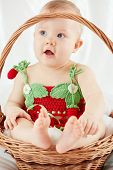Portrait of funny little girl with open mouth dressed in strawberry suit sitting in wicker basket on white coverlet