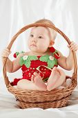 Portrait of little girl dressed in strawberry suit sitting in wicker basket and holding on to basket handle