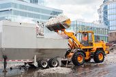 stock photo of flux  - Bulldozer loads snow to truck for snow melting on street in city at cloudy day - JPG