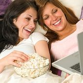 Pretty sisters lying on bed watching funny movie