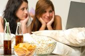 stock photo of slumber party  - Young girls having slumber party and watching movies - JPG