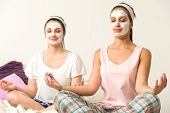 Meditating women sitting cross-legged  wearing white facial mask