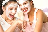 Laughing caucasian girls wearing peeling mask having fun