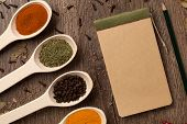 Old notebook, spices in spoons on wooden background