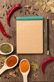 Red chili peppers, spices in spoons, notebook paper and pencil on oak wood texture background