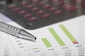 stock photo of waste reduction  - Detail of Accountancy graphics and calculator in white background - JPG