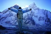 Man facing Mount Everest (8848m) and Nuptse Mountain (7861m) just before sunrise, standing on the Ka