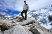 Man standing at Mount Everest Base Camp with the black rock pyramide of Mount Everest (8848m) in the
