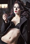 foto of navel  - Closeup portrait of sexy smoking vamp woman in black underwear and coat - JPG