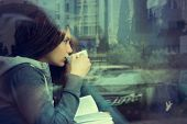 Young woman drinking coffee and reading book sitting indoor in urban cafe. Cafe city lifestyle. Casu