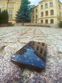 stock photo of cobblestone  - A touch screen mobile phone with broken screen lying on the cobblestone pavement - JPG