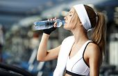 stock photo of treadmill  - Smiling athletic woman drinking water on a treadmill - JPG