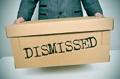 a businessman carrying a box with the word dismissed written in it