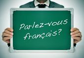 man wearing a suit holding a chalkboard with the question parlez-vous francais? do you speak french?