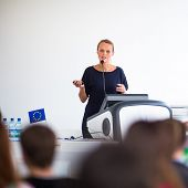 Pretty, young business woman giving a presentation in a conference/meeting setting (shallow DOF; col