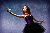 image of dancing rain  - Young woman dancing in the rain - JPG
