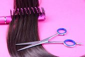 Long brown hair with hairbrush and scissors on pink background