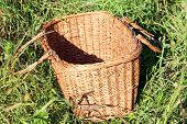 Opened picnic basket in the grass.
