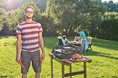Man, posing next to a barbecue, holding a fork and pliers, with a group of friends sitting around a