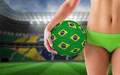 Fit girl in green bikini holding brazil football against large football stadium with brasilian fans