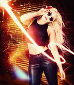 stock photo of starlet  - Nightclub trance girl dancing around a 1970 disco club of bright lights stars and glitter wearing sunglasses tank top and leather jeans - JPG