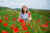 Girl Gathering Poppies On The Field In Auvergne