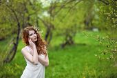 Red-haired girl in a spring garden