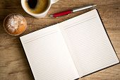 open blank notebook and cup of coffee on old wooden table
