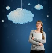 Beautiful young woman looking at hanging clouds, daydream