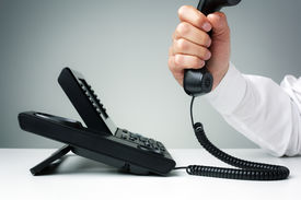 stock photo of keypad  - businessman on business landline telephone in an office concept for communication - JPG